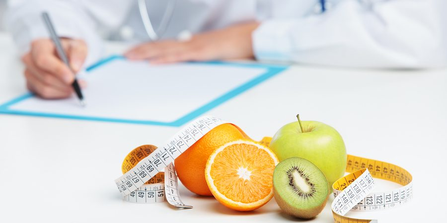 Nutritionist Doctor is writing a prescription. Focus on fruit ** Note: Shallow depth of field