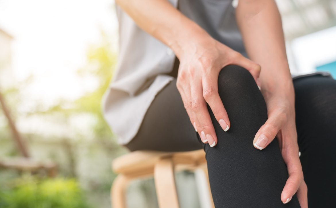 A young woman massaging her painful knee