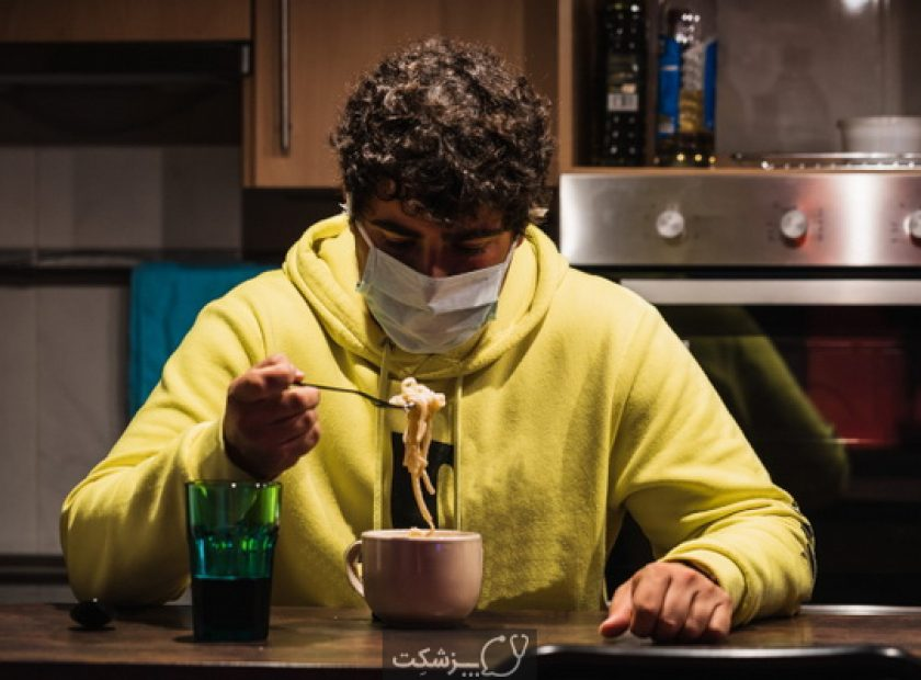 Young spanish man tries to eat wearing a mask while wearing a mask protecting to coronavirus COVID-19 due to hysteria and panic caused by media and governments a very contagious virus